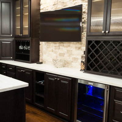 Inspiration for a mid-sized contemporary galley dark wood floor seated home bar remodel in Indianapolis with dark wood cabinets, solid surface countertops, beige backsplash, stone tile backsplash, an undermount sink and raised-panel cabinets