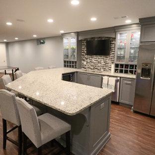ルイビルの巨大なコンテンポラリースタイルのおしゃれな着席型バー (コの字型、アンダーカウンターシンク、ガラス扉のキャビネット、グレーのキャビネット、御影石カウンター、マルチカラーのキッチンパネル、ボーダータイルのキッチンパネル、無垢フローリング、茶色い床、グレーのキッチンカウンター) の写真