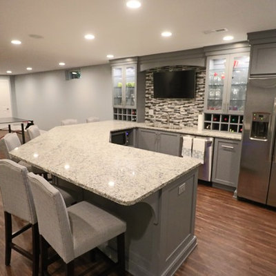 Seated home bar - huge contemporary u-shaped medium tone wood floor and brown floor seated home bar idea in Louisville with an undermount sink, glass-front cabinets, gray cabinets, granite countertops, multicolored backsplash, matchstick tile backsplash and gray countertops