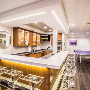 ニューヨークの広いモダンスタイルのおしゃれな着席型バー (コの字型、アンダーカウンターシンク、ガラス扉のキャビネット、中間色木目調キャビネット、人工大理石カウンター、白いキッチンパネル、塗装フローリング、茶色い床) の写真