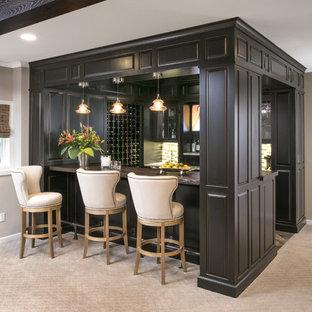 Immagine di un grande bancone bar classico con moquette, pavimento grigio, lavello sottopiano, ante con bugna sagomata, ante nere, top in legno e paraspruzzi multicolore