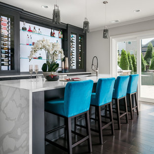 Inspiration for a huge contemporary galley dark wood floor and brown floor seated home bar remodel in Atlanta with an undermount sink, flat-panel cabinets, black cabinets, quartz countertops, white countertops and glass sheet backsplash