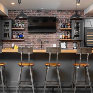 フィラデルフィアの広いインダストリアルスタイルのおしゃれな着席型バー (ll型、アンダーカウンターシンク、シェーカースタイル扉のキャビネット、グレーのキャビネット、木材カウンター、マルチカラーのキッチンパネル、レンガのキッチンパネル、クッションフロア、ベージュの床、ベージュのキッチンカウンター) の写真