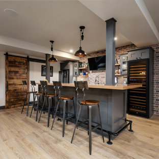 Example of a large urban galley vinyl floor and beige floor seated home bar design in Philadelphia with an undermount sink, shaker cabinets, gray cabinets, wood countertops, multicolored backsplash, brick backsplash and beige countertops
