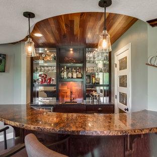 Immagine di un bancone bar chic di medie dimensioni con lavello sottopiano, ante in stile shaker, ante in legno bruno, top in granito, paraspruzzi a specchio, parquet scuro, pavimento marrone e top beige