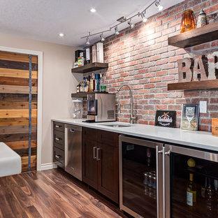 Esempio di un angolo bar rustico di medie dimensioni con pavimento in laminato e pavimento marrone