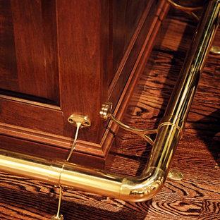 Esempio di un grande bancone bar chic con lavello sottopiano, ante con bugna sagomata, ante in legno scuro, top in granito, paraspruzzi beige, paraspruzzi con piastrelle in pietra e pavimento in legno massello medio