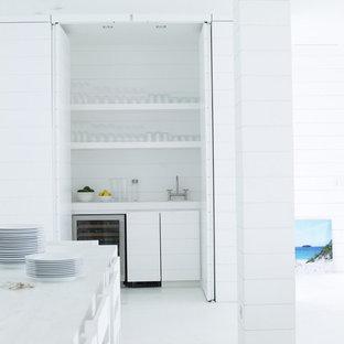 Idee per un piccolo armadio bar tropicale con pavimento in cemento, ante lisce, ante bianche, paraspruzzi bianco, pavimento bianco, lavello da incasso e paraspruzzi in legno