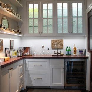Ejemplo de bar en casa con fregadero en L, costero, pequeño, con fregadero bajoencimera, armarios estilo shaker, puertas de armario blancas, encimera de madera y encimeras marrones