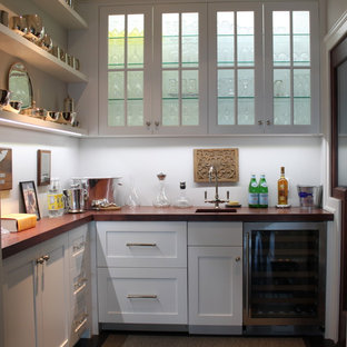 Wet bar - small beach style l-shaped wet bar idea in Boston with an undermount sink, shaker cabinets, white cabinets, wood countertops and brown countertops