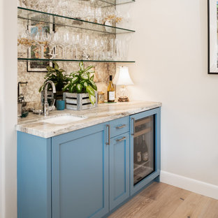 Inspiration for a small traditional galley wet bar in San Francisco with a submerged sink, shaker cabinets, blue cabinets, marble worktops, mirror splashback, light hardwood flooring, brown floors and grey worktops.
