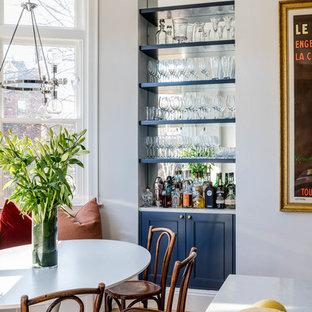 ボストンの小さいトランジショナルスタイルのおしゃれなホームバー (青いキャビネット、淡色無垢フローリング、I型、シンクなし、オープンシェルフ、ミラータイルのキッチンパネル、白いキッチンカウンター) の写真