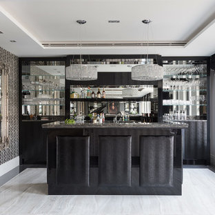 Medium sized contemporary galley wet bar in Hertfordshire with a submerged sink, flat-panel cabinets, black cabinets, granite worktops, mirror splashback, black worktops and grey floors.