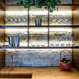 Inspiration for a rustic wet bar remodel in Denver with an undermount sink, recessed-panel cabinets, brown cabinets, wood countertops, brown countertops and gray backsplash
