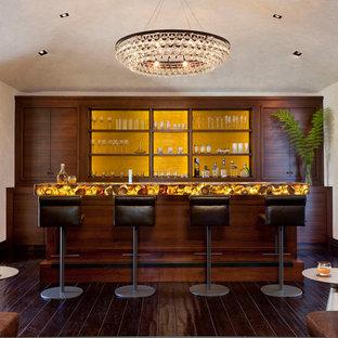 Foto di un bancone bar mediterraneo con ante in legno bruno, paraspruzzi giallo, parquet scuro, top giallo e ante lisce