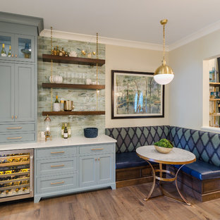 Modelo de bar en casa en L, tradicional, de tamaño medio, con fregadero bajoencimera, armarios con rebordes decorativos, puertas de armario azules, encimera de cuarzo compacto, salpicadero multicolor, salpicadero de azulejos de vidrio y suelo de madera en tonos medios
