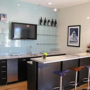 タンパのコンテンポラリースタイルのおしゃれな着席型バー (ll型、アンダーカウンターシンク、フラットパネル扉のキャビネット、黒いキャビネット、青いキッチンパネル、ガラス板のキッチンパネル、無垢フローリング) の写真