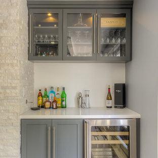 ロサンゼルスの小さいトランジショナルスタイルのおしゃれなホームバー (I型、シェーカースタイル扉のキャビネット、グレーのキャビネット、無垢フローリング、白いキッチンカウンター) の写真