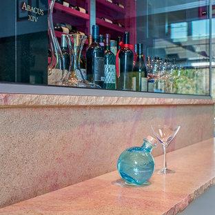 Immagine di un angolo bar moderno con ante di vetro, top in pietra calcarea, paraspruzzi beige, paraspruzzi con piastrelle di vetro e top rosa