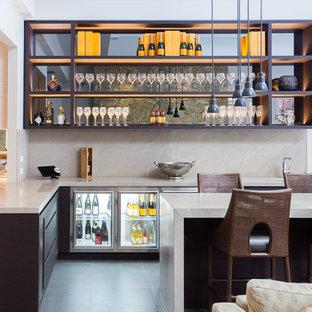 Ispirazione per un grande bancone bar minimal con ante in legno bruno, paraspruzzi beige, paraspruzzi in lastra di pietra, pavimento grigio, top grigio e nessun'anta