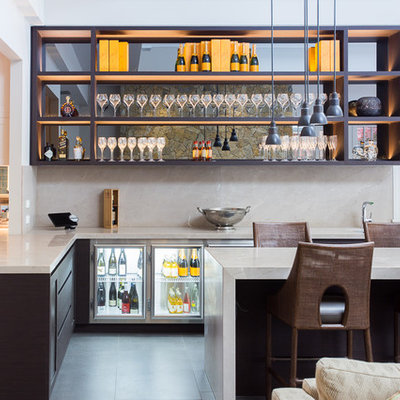Seated home bar - large contemporary l-shaped gray floor seated home bar idea in Melbourne with dark wood cabinets, beige backsplash, stone slab backsplash, gray countertops and open cabinets