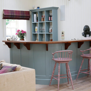 Traditional breakfast bar in Other with blue cabinets, wood worktops and brown worktops.