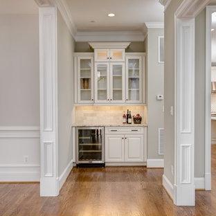 ワシントンD.C.の小さいトラディショナルスタイルのおしゃれなホームバー (I型、レイズドパネル扉のキャビネット、ベージュのキャビネット、御影石カウンター、ベージュキッチンパネル、トラバーチンのキッチンパネル、無垢フローリング) の写真