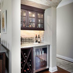 Cette image montre un petit bar de salon avec évier linéaire traditionnel avec un évier posé, un placard à porte shaker, des portes de placard en bois sombre, un plan de travail en granite, une crédence beige, une crédence en carrelage de pierre et un sol en bois brun.