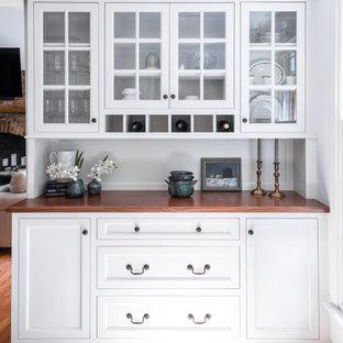 Foto di un piccolo angolo bar tradizionale con nessun lavello, consolle stile comò, ante bianche, top in legno e pavimento in legno massello medio