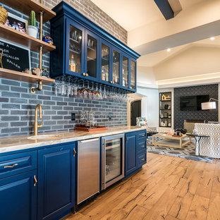 フェニックスのコンテンポラリースタイルのおしゃれなウェット バー (I型、アンダーカウンターシンク、レイズドパネル扉のキャビネット、青いキャビネット、グレーのキッチンパネル、レンガのキッチンパネル、無垢フローリング、茶色い床、ベージュのキッチンカウンター) の写真