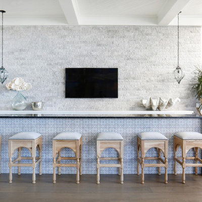 Example of a beach style medium tone wood floor seated home bar design in Orange County with black countertops