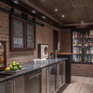 デトロイトの広いインダストリアルスタイルのおしゃれな着席型バー (クッションフロア、ベージュの床、アンダーカウンターシンク、黒いキャビネット、木材カウンター、赤いキッチンパネル、茶色いキッチンカウンター、ll型、レンガのキッチンパネル) の写真