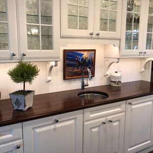 This is an example of a medium sized traditional u-shaped wet bar in Philadelphia with a submerged sink, glass-front cabinets, white cabinets, wood worktops, white splashback, wood splashback, medium hardwood flooring and brown worktops.