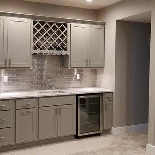 Immagine di un angolo bar con lavandino american style di medie dimensioni con lavello sottopiano, ante in stile shaker, ante grigie, top in marmo, paraspruzzi grigio, paraspruzzi con piastrelle di metallo, moquette e pavimento beige