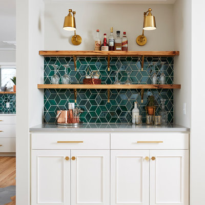 Example of a transitional single-wall light wood floor and beige floor home bar design in Minneapolis with white cabinets, ceramic backsplash, no sink, recessed-panel cabinets, green backsplash and gray countertops