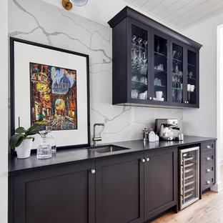 Ispirazione per un grande angolo bar con lavandino chic con lavello sottopiano, ante in stile shaker, top in quarzo composito, paraspruzzi bianco, ante nere, paraspruzzi in lastra di pietra, top nero e parquet chiaro