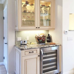 Medium sized traditional l-shaped home bar in San Diego with a submerged sink, recessed-panel cabinets, white cabinets, granite worktops, beige splashback, glass tiled splashback and light hardwood flooring.