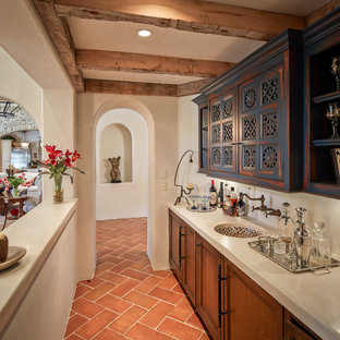 Inspiration for a mediterranean single-wall terra-cotta tile and orange floor wet bar remodel in Houston with an undermount sink, recessed-panel cabinets and distressed cabinets