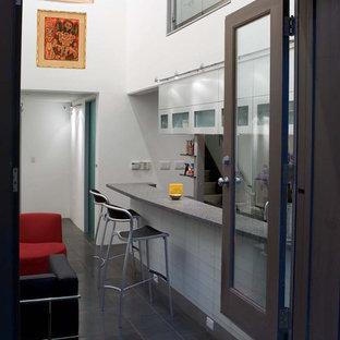 Esempio di un bancone bar moderno di medie dimensioni con lavello sottopiano, top in vetro riciclato, paraspruzzi bianco, pavimento in gres porcellanato, paraspruzzi con piastrelle di vetro e ante di vetro