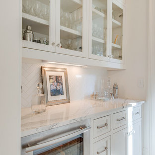 Photo of a medium sized traditional single-wall wet bar in Nashville with recessed-panel cabinets, white cabinets, engineered stone countertops, white splashback, porcelain splashback, medium hardwood flooring and brown floors.