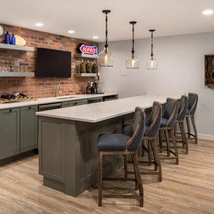 ワシントンD.C.の中くらいのインダストリアルスタイルのおしゃれな着席型バー (ラミネートの床、茶色い床、ll型、アンダーカウンターシンク、シェーカースタイル扉のキャビネット、グレーのキャビネット、赤いキッチンパネル、レンガのキッチンパネル、グレーのキッチンカウンター) の写真