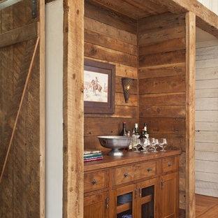 他の地域の小さいラスティックスタイルのおしゃれなホームバー (I型、シンクなし、家具調キャビネット、中間色木目調キャビネット、木材カウンター、無垢フローリング) の写真
