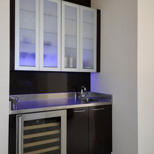 Immagine di un piccolo angolo bar con lavandino minimal con lavello integrato, ante di vetro, ante marroni, top in acciaio inossidabile, paraspruzzi marrone, paraspruzzi con lastra di vetro, pavimento con piastrelle in ceramica e pavimento bianco