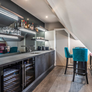This is an example of a contemporary single-wall wet bar in Berkshire with a built-in sink, flat-panel cabinets, grey cabinets, mirror splashback, medium hardwood flooring, brown floors and grey worktops.