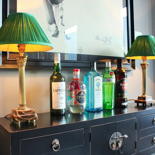 Inspiration for a small eclectic single-wall home bar in London with freestanding cabinets, black cabinets, wood worktops and black worktops.