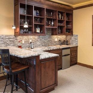 Immagine di un bancone bar stile rurale di medie dimensioni con lavello sottopiano, ante a filo, ante in legno bruno, top in granito, paraspruzzi grigio, paraspruzzi con piastrelle di vetro e moquette