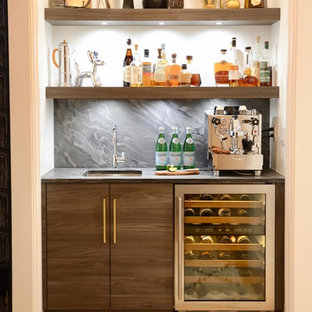 Example of a mid-sized trendy single-wall light wood floor and beige floor wet bar design in New York with flat-panel cabinets, medium tone wood cabinets, soapstone countertops, gray backsplash, an undermount sink and gray countertops
