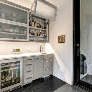 Idee per un angolo bar con lavandino design con lavello sottopiano, ante lisce, ante grigie, paraspruzzi grigio, pavimento nero e top bianco