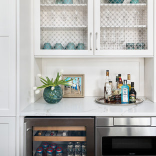 This is an example of a small classic single-wall home bar in Chicago with no sink, white cabinets, white splashback, white worktops and marble worktops.