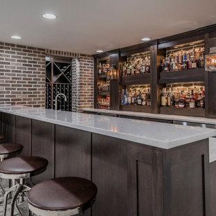 Immagine di un bancone bar country con ante in stile shaker, ante in legno bruno, paraspruzzi in mattoni, moquette e pavimento grigio